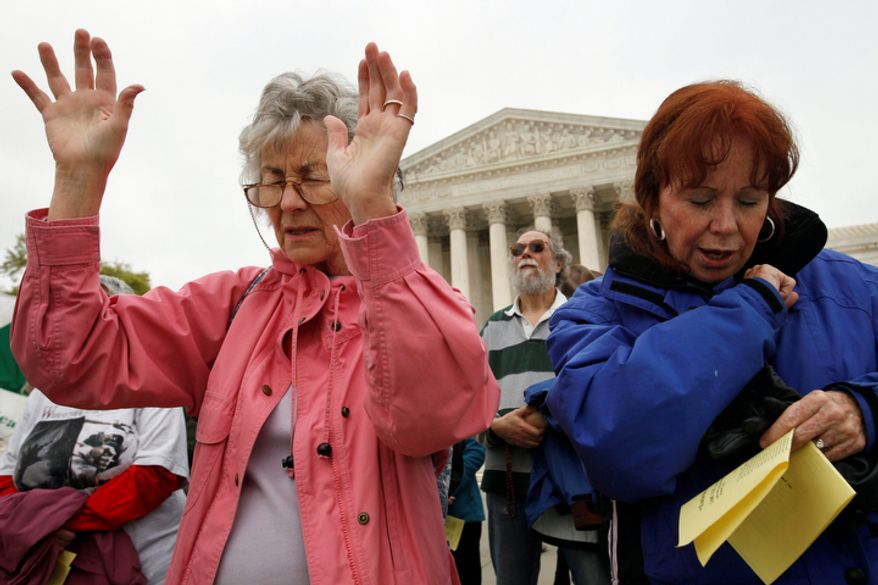 "Joan Schnabel of Annapolis, Md., left, and Marge Groetsch of Front Royal, Va., pray in front of the Supreme Court as part of ""Encircle the Court in Prayer,"" an event led by Christian faith organizations. (AP Photo/Jacquelyn Martin)"