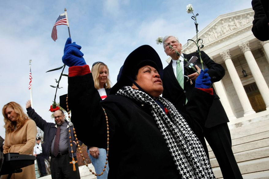 Minh Chau Levan of Arlington, Va., prayers with other members of Christian faith organizations in front of the Supreme Court. (AP Photo/Jacquelyn Martin)