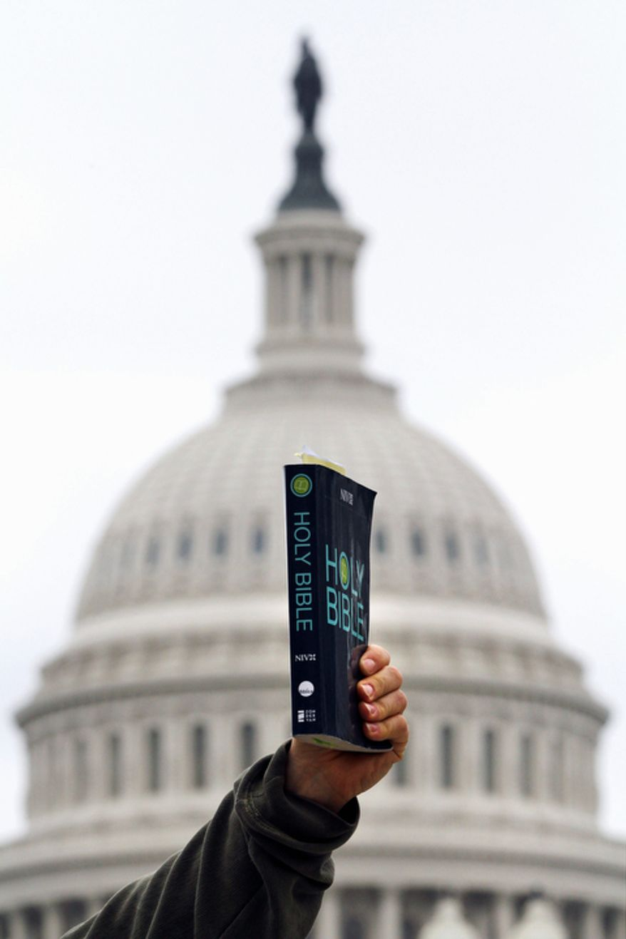 A Bible is held in the air near the U.S. Capitol on the eve of the Supreme Court arguments on President Obama's health care legislation, in Washington, on Sunday, March 25, 2012. (AP Photo/Jacquelyn Martin)