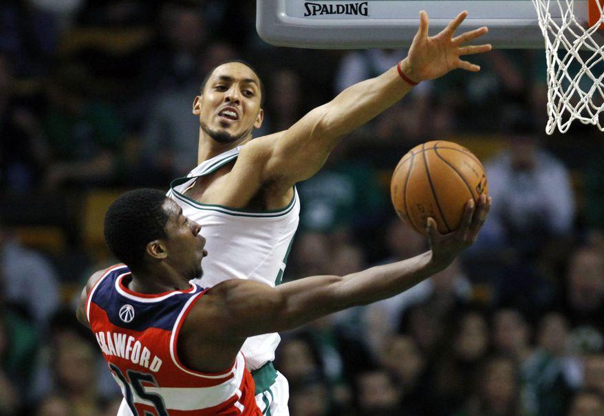 Washington Wizards' Jordan Crawford (15) shoots against Boston Celtics' Ryan Hollins in the second quarter of an NBA basketball game in Boston, Sunday, March 25, 2012. (AP Photo/Michael Dwyer)