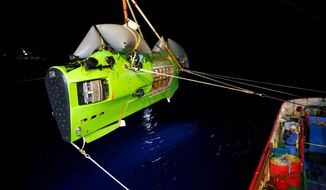 The Deepsea Challenger submersible with James Cameron inside is moved into place to begin its descent 7 miles below the surface of the Pacific Ocean to the Mariana Trench. The movie director spent more than three hours inside the trench. (National Geographic via Associated Press)