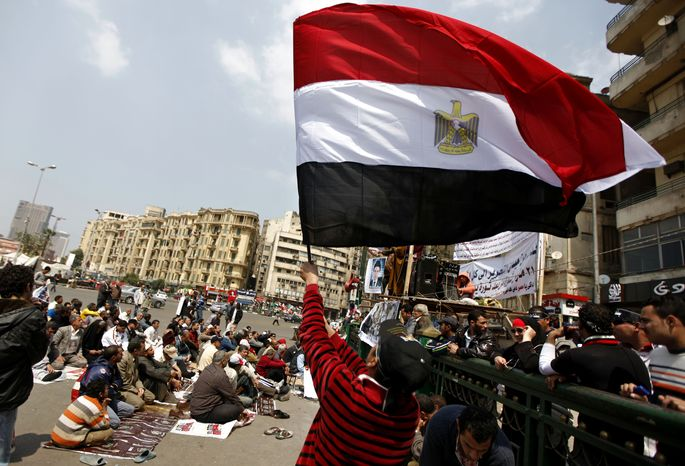 An Egyptian protester waves the national flag March 23, 2012, as others attend the Friday noon prayer in Cairo's Tahrir Square. (Associated Press)