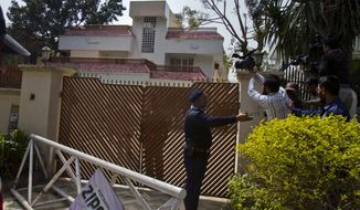 Pakistani police officers stop cameramen from filming a house where family members of slain al Qaeda leader Osama bin Laden are believed to be held on Saturday, March 17, 2012, in Islamabad. (AP Photo/Anjum Naveed)