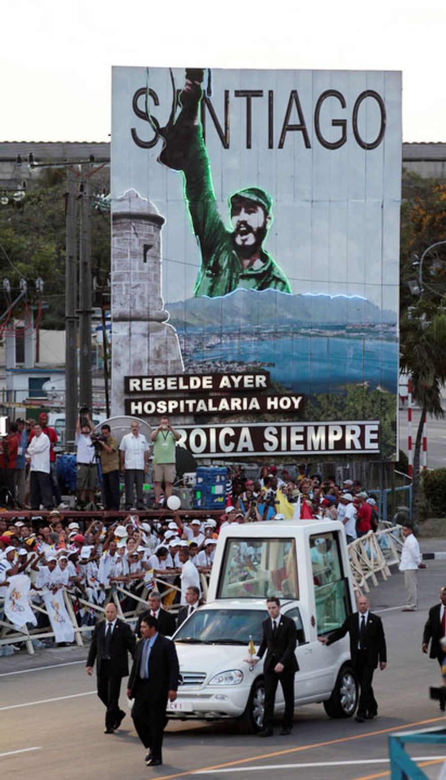 With a billboard showing Cuba's leader Fidel Castro in the background, Pope Benedict XVI arrives aboard the popemobile in Revolution Square to celebrate a Mass in Santiago de Cuba, Cuba, on March 26, 2012. The pope is in Cuba for a three-day visit. (Associated Press)