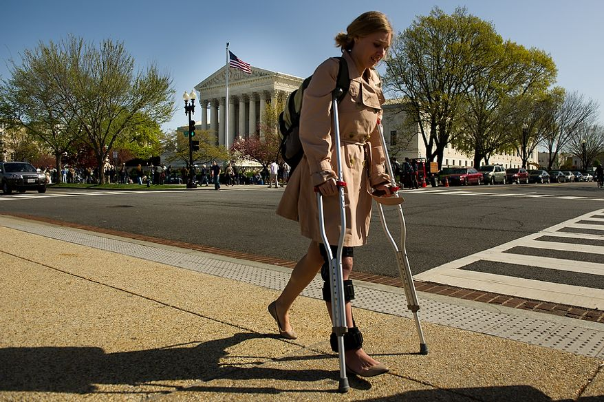 Lydia Mitts, an analyst for health-care advocacy organization Families USA, is seen March 26, 2012, outside the U.S. Supreme Court building in D.C., as the court hears oral arguments on the challenges to the Affordable Care Act. Mitts, who supports the Affordable Care Act, walked with the aid of crutches after recent knee surgery. (Andrew Harnik/The Washington Times)