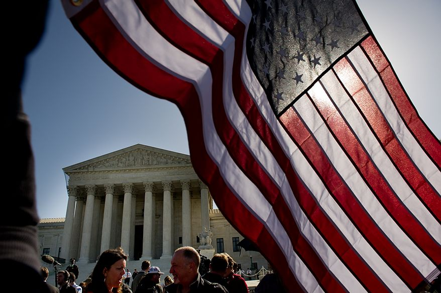 American flags are waved March 26, 2012, in front of the U.S. Supreme Court building in D.C. as the court hears oral arguments on the challenges to the Affordable Care Act. (Andrew Harnik/The Washington Times)