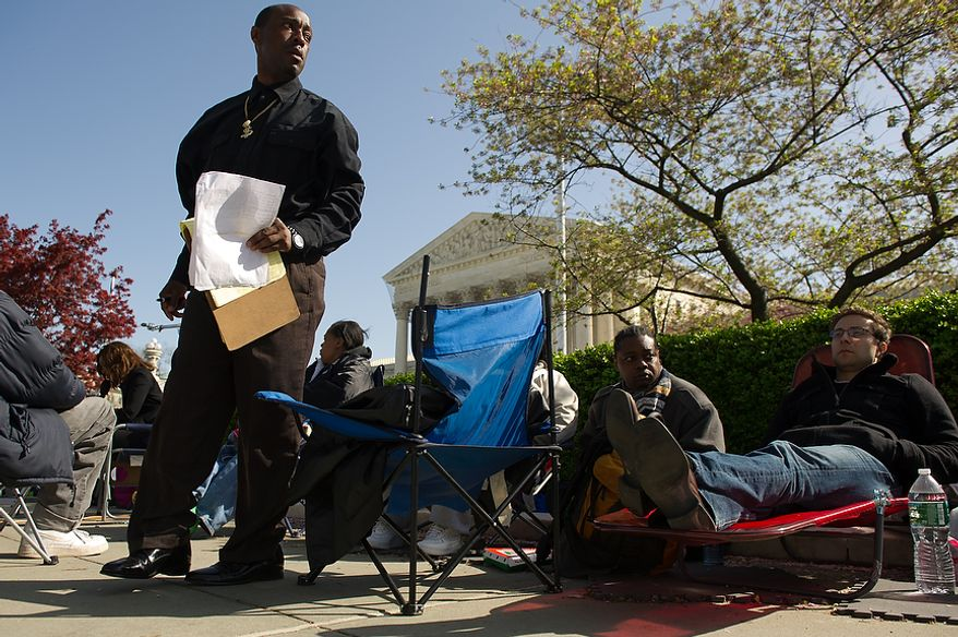 John Spears (standing), a supervisor for courier company Quality Messenger Service, makes a list March 26, 2012, of the employees he has hired to hold a place in line outside the U.S. Supreme Court building in D.C., for a chance to watch as the court hears oral arguments on the challenges to the Affordable Care Act. Brook Silva-Braga (right), of New York City, had been waiting in line for the previous two days. (Andrew Harnik/The Washington Times)