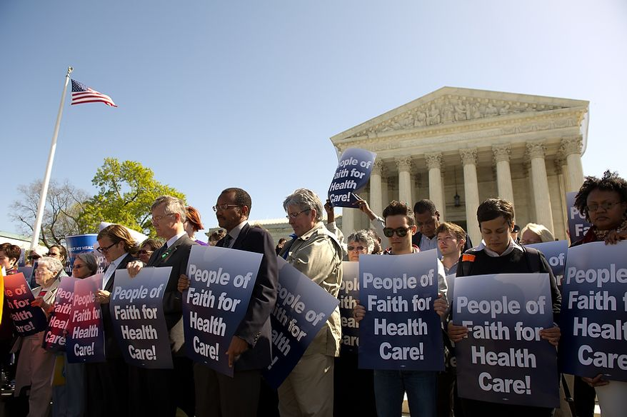 "Demonstrators holding signs reading ""People of faith for health care"" gather in front of the U.S. Supreme Court building in D.C., on March 26, 2012, to ""pray for moral discernment"" as the court hears oral arguments on the challenges to the Affordable Care Act, Washington, D.C. (Andrew Harnik/The Washington Times)"