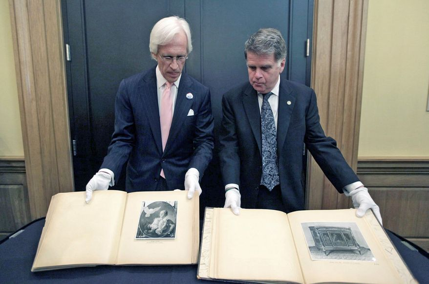 David S. Ferriero, archivist of the United States, right, and Robert M. Edsel, founder and president of Monuments Men Foundation for the Preservation of Art show two newly discovered albums containing photographs of art works and furniture stolen by the Nazis during World War II after they were unveiled at a news conference in the Meadows Museum at SMU in Dallas, Tuesday, Feb. 27, 2012. The Dallas-based Monuments Men Foundation for the Preservation of Art had been contacted by relatives of two World War II soldiers who took the albums from Hitler's home. They'll be donated to the U.S. National Archives. (AP Photo/LM Otero)