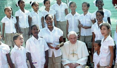 Pope Benedict XVI is greeted by children during his visit to the sanctuary of the Virgin of Charity of Cobre, Cuba's patron saint, in the little town of El Cobre, outside of Santiago, on Tuesday. Benedict is on the second day of his Cuban tour. (Associated Press)