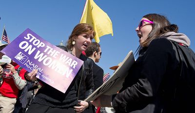 Lauren Kurtz (left), a George Washington student who supports President Obama's health care law, and Keli Carender, a Seattle resident against the law, demonstrate outside the Supreme Court on Tuesday. The justices were hearing arguments on the law's individual mandate. (Barbara L. Salisbury/The Washington Times)
