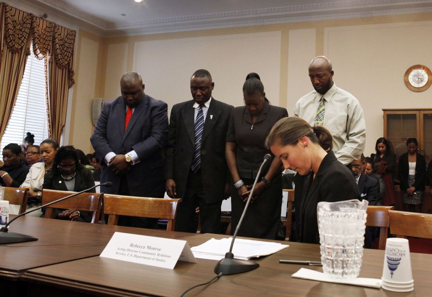 Daryl Parks (from left), president of the National Bar Association; the Martin family lawyer, Benjamin Crump; and Trayvon Martin's parents, Tracy Martin and Sybrina Fulton, stand during a moment of prayer for Trayvon during a House Judiciary Committee Democratic briefing on racial profiling and hate crimes on Capitol Hill in Washington on Tuesday, March 27, 2012. In front is Rebecca Monroe of the Department of Justice. (AP Photo/Jacquelyn Martin)