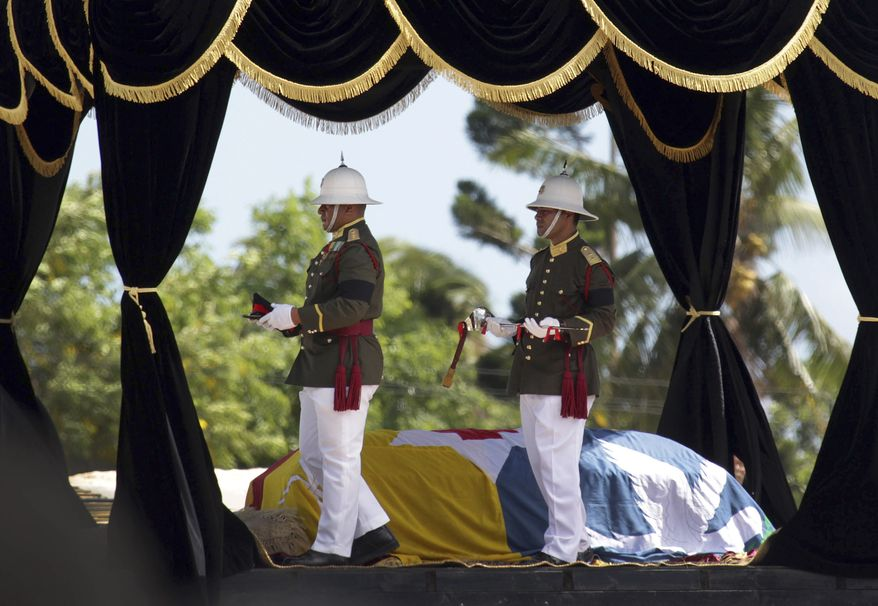 Ceremonial guards walk past the casket of Tonga's late King George Tupou V during his funeral procession in Nuku-alofa, Tonga, on March 27, 2012. (Associated Press/New Zealand Herald, Sarah Ivey)