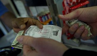 A customer buys Mega Millions tickets at the Exxon station at the base of the Key Bridge in Georgetown on Wednesday, hoping that little piece of paper will become hundreds of millions of dollars. (Barbara L. Salisbury/The Washington Times)