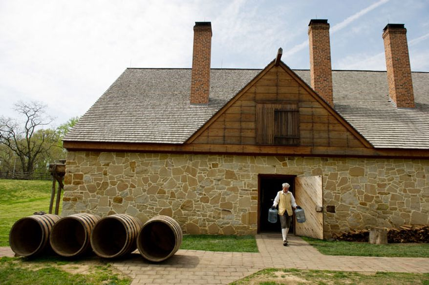 Eric Barton, an Historic Trade Interpreter with Mount Vernon, carries out plastic jugs to be washed after the Mount Vernon historic distillers produce a scotch style single malt whisky made using colonial style stills at George Washington's reconstructed distillery. (Andrew Harnik/The Washington Times)