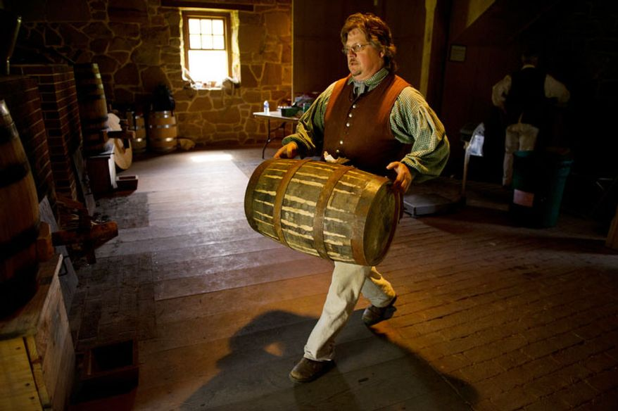 Steve Bashore, Manager of Historic Trades at Mount Vernon, moves an oak barrel full of scotch style single malt whisky into storage. The oak barrels will be aged for three years and then auctioned for charities around the world. (Andrew Harnik/The Washington Times)