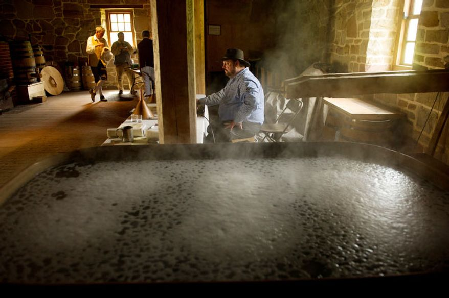 Hot water steams in a historical 210 gallon copper boiler as Dave Pickerell, Master Distiller for Mount Vernon, center, takes inventory of the barrels of scotch style single malt whisky as his crew of historic distillers break for lunch. (Andrew Harnik/The Washington Times)
