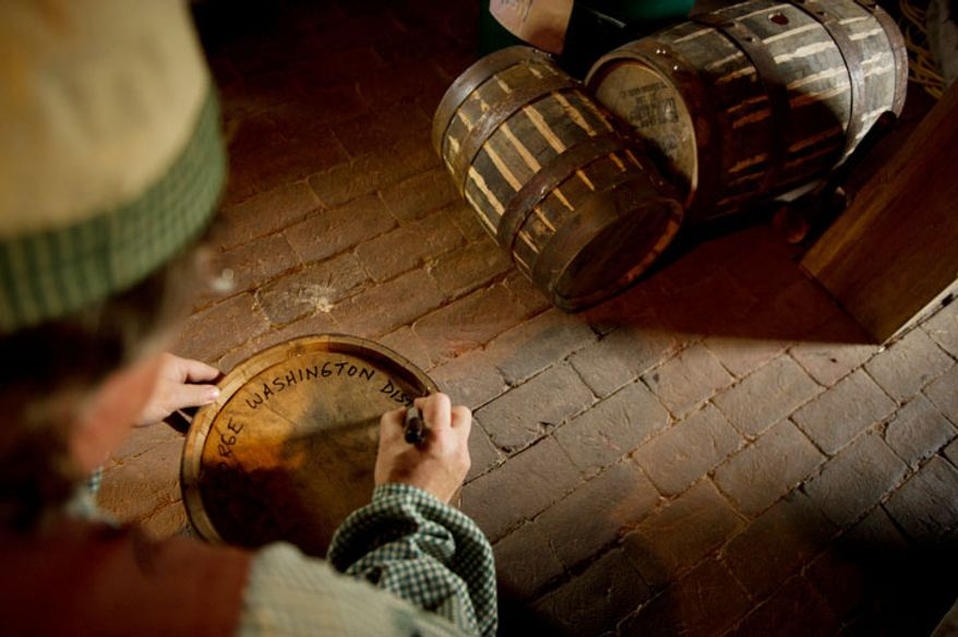 Steve Bashore, Manager of Historic Trades at Mount Vernon, writes down identifying information on an oak barrel of scotch style single malt whisky. (Andrew Harnik/The Washington Times)