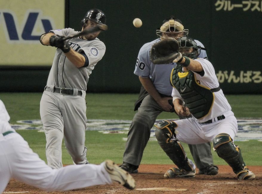 Dustin Ackley of the Seattle Mariners hits an RBI single in front of Oakland Athletics catcher Kurt Suzuki in the 11th inning of their American League season-opening baseball game at the Tokyo Dome in Tokyo on Wednesday, March 28, 2012. Seattle won 3-1. (AP Photo/Itsuo Inouye)
