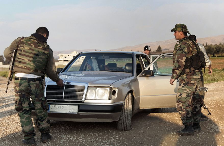 Lebanese soldiers search a car during a raid at the Lebanese-Syrian border town of Qaa, in northeastern Lebanon, on Tuesday, March 27, 2012. (AP Photo/Hussein Malla)