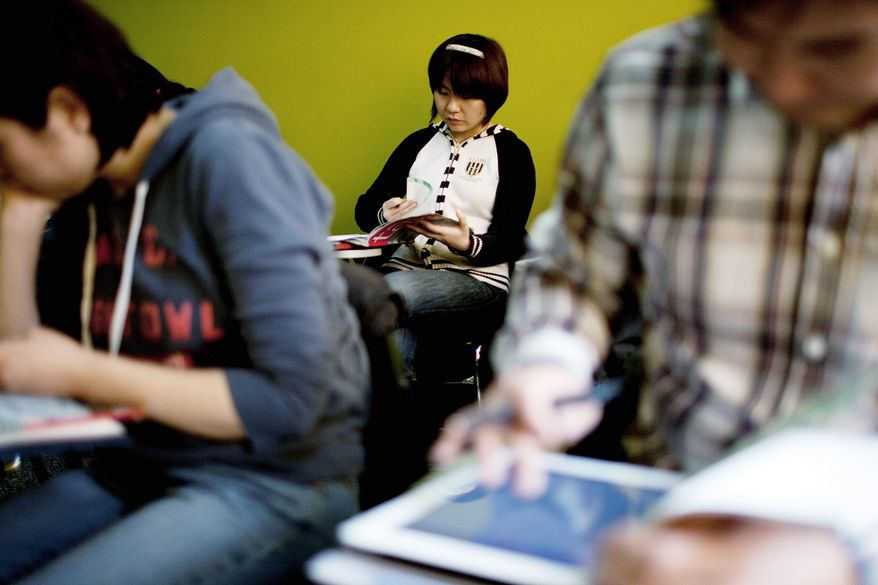 Yin Shanshan, who plans to study for a master's degree in Canada, checks her textbook during a French course of Alliance Francaise, an organization that promotes French language and culture, in Tianjin, China. Thousands of people in China are trying to gain enough proficiency in French to emigrate to Quebec. (Associated Press)
