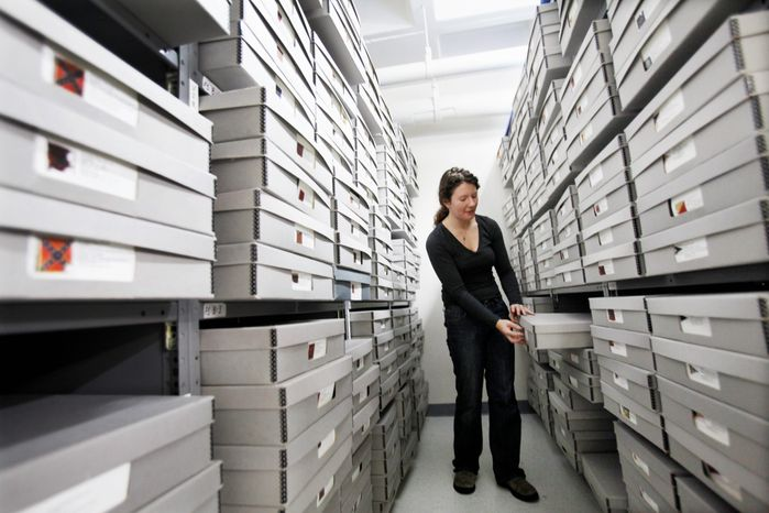 ** FILE ** In this Feb. 24, 2012, photo, Cathy Wright, curator at the Museum of the Confederacy, opens a box in the flag room, which houses hundreds of original civil war battle flags in Richmond, Va. (AP Photo/Richmond Times-Dispatch, Dean Hoffmeyer)