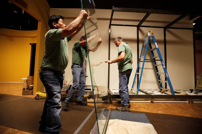 ** FILE ** In this Feb. 13, 2012, photo, Teng Phung, left, Chris Lugt, center, and Jim Slingo lift a glass panel destined for a display window in the new Museum of the Confederacy in Richmond, Va. (AP Photo/Richmond Times-Dispatch, Dean Hoffmeyer)