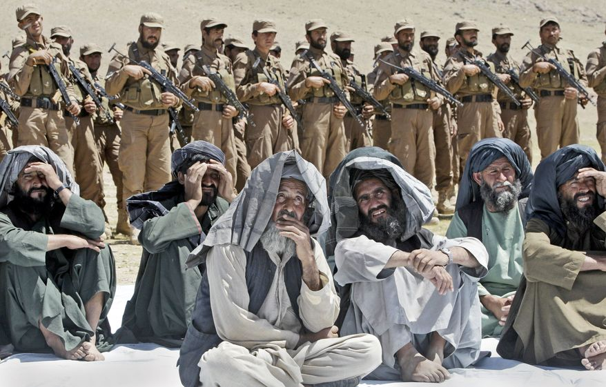 Villagers join Afghan Local Police on Thursday, March 29, 2012, for a ceremony in Gizab at which new uniforms were presented. Commanders think the units are capable of holding villages after NATO troops clear out the enemy. (Associated Press)