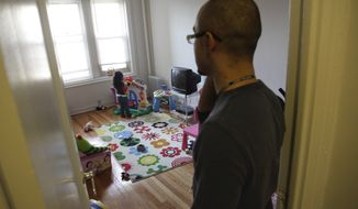 Christopher Astacio stands in the doorway watching as his daughter Cristina, 2, recently diagnosed with a mild form of autism, plays in her bedroom on Wednesday, March 28, 2012 in New York. (AP Photo/Bebeto Matthews)