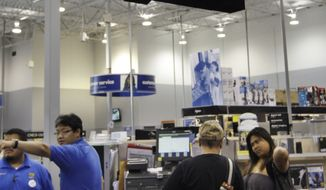 **FILE** Employees help out customers Sept. 12, 2011, at a Best Buy store in Mountain View, Calif. (Associated Press)