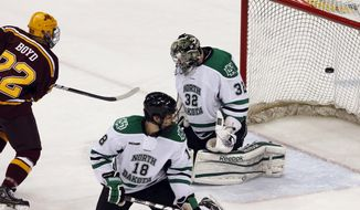 Minnesota's Travis Boyd (22) scores on North Dakota goalie Aaron Dell (32) during the second period of the NCAA men's college hockey tournament West Regional final, Sunday, March 25, 2012, in St. Paul, Minn. In the foreground is North Dakota's Dillon Simpson. (AP Photo/Genevieve Ross)