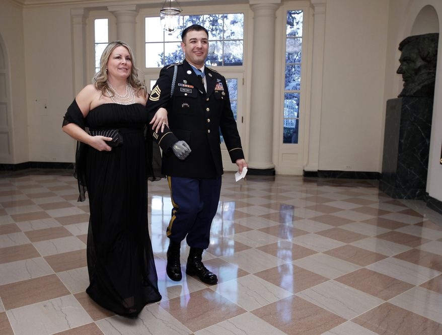 **FILE** Medal of Honor recipient Sgt. 1st Class Leroy Petry and his wife, Ashley, arrive March 14, 2012, at the Booksellers area of the White House for the State Dinner hosted by President Obama and first lady Michelle Obama for British Prime Minister David Cameron and his wife Samantha. (Associated Press)