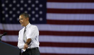 President Obama rolls up his sleeves as he speaks March, 30, 2012, at a campaign fundraiser at the University of Vermont in Burlington, Vt. (Associated Press)