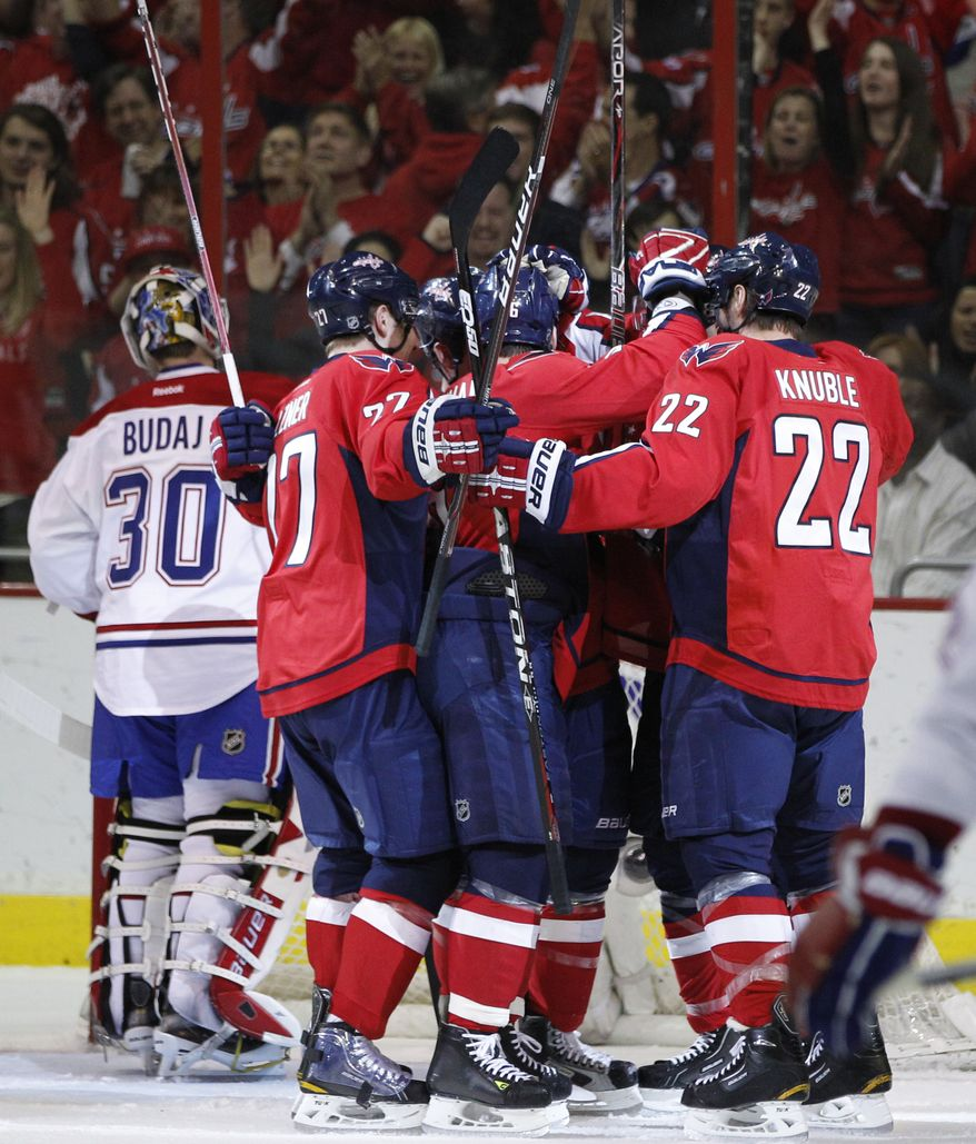 The Washington Capitals celebrate after center Jay Beagle scored a goal against Montreal Canadiens goalie Peter Budaj (30) during the first period of an NHL hockey game on Saturday, March 31, 2012 in Washington. (AP Photo/Evan Vucci)