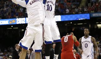 Kansas guard Tyshawn Taylor (10) celebrates with Kansas guard Christian Garrett at the end of an NCAA Final Four tournament game against Ohio State Saturday, March 31, 2012, in New Orleans. Kansas won 64-62 to advance to the national title game versus Kentucky. (AP Photo/David J. Phillip)