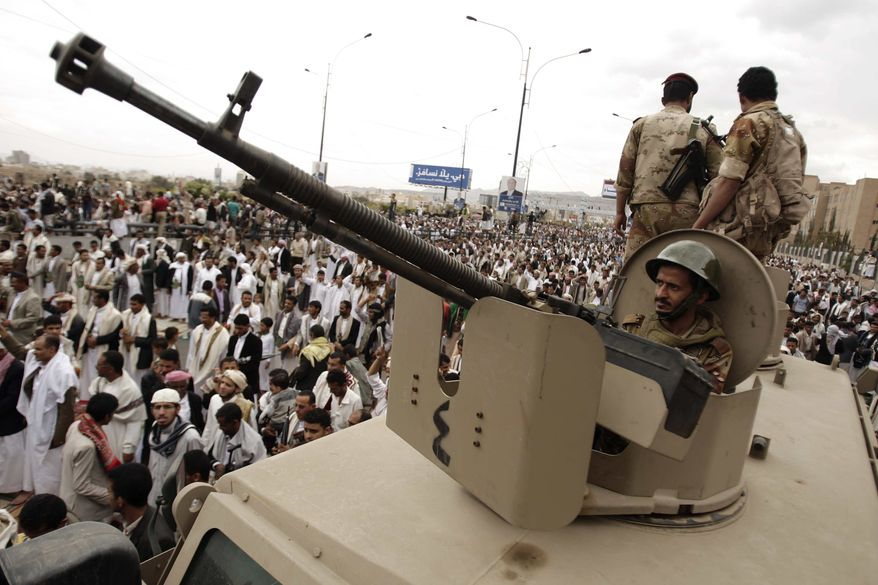 A defected army soldier supporting protestors looks on from behind a weapon mounted on a patrol truck to secure a street where protestors demand the trial of Yemen's former President Ali Abdullah Saleh, in Sanaa, Yemen, Friday, March 30, 2012. (AP Photo/Hani Mohammed)