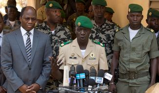 Mali coup leader Capt. Amadou Haya Sanogo (center), accompanied by Burkina Faso Foreign Affairs Minister Djibril Bassole (left), speaks during a news conference Sunday in Kati. Capt. Sanogo announced he is reinstating the nation's constitution. (Associated Press)