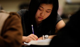 Sally Kim takes notes during a physics class at Columbia Independent School in Columbia, Mo., on Wednesday, Feb. 27, 2012. Miss Kim's parents, who live in South Korea, sent her to live with relatives in Columbia for a better education that provides more collegiate opportunities. (AP Photo/Grant Hindsley)