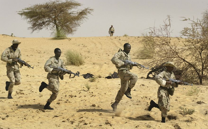 ** FILE ** Malian soldiers from the 512th Motorized Infantry Company complete their training by U.S. Special Forces (top) in the desert near Timbuktu in Mali in March 2004 as part of the U.S. Pan-Sahel Initiative to secure the Sahel region from being used by terrorists. (AP Photo/Ben Curtis)