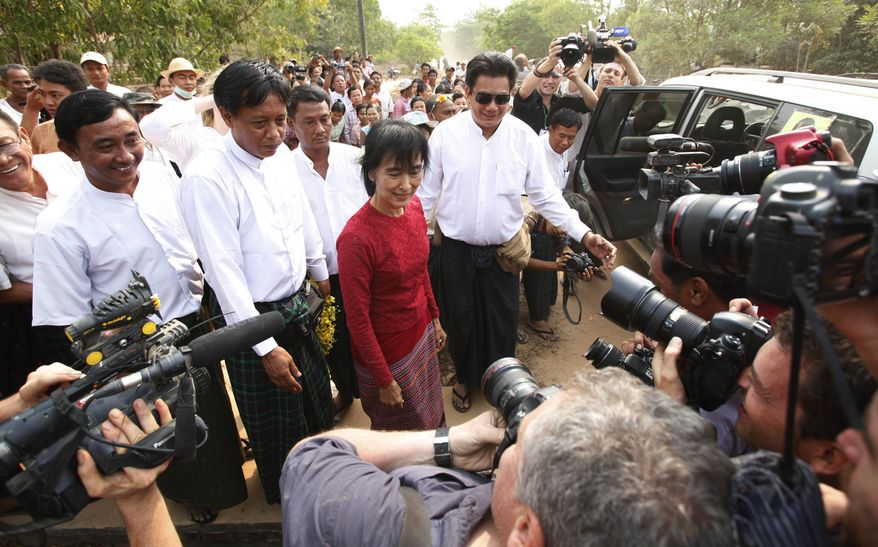Aung San Suu Kyi (center), Myanmar's pro-democracy leader, pauses for journalists outside a polling station on the outskirts of Yangon, Myanmar, on Sunday, April 1, 2012. (AP Photo)