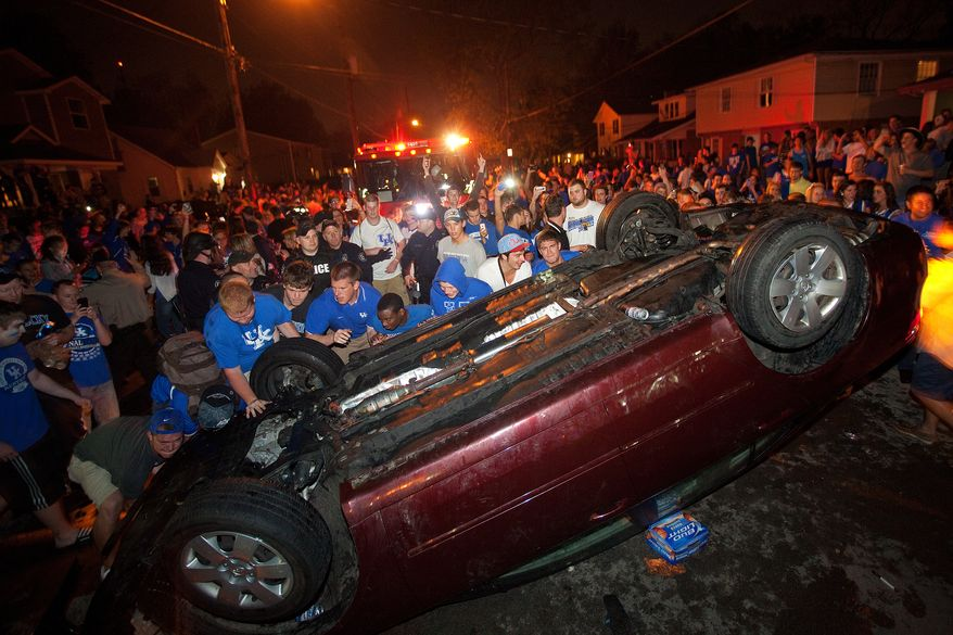University of Kentucky fans flip a car on State Street in Lexington, Ky., as they celebrate Kentucky's 69-61 win over cross-state rival Louisville in an NCAA Final Four semifinal college basketball tournament game on Saturday, March 31, 2012. (AP Photo/Lexington Herald-Leader, Jonathan Palmer)