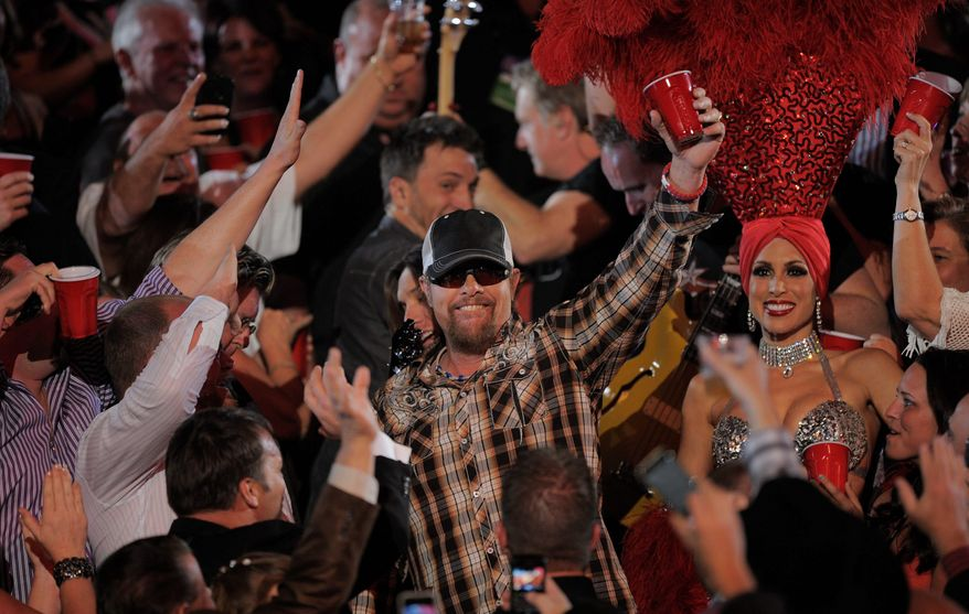 """Toby Keith takes his """"Red Solo Cup,"""" winner of the video of the year award at Sunday's Academy of Country Music Awards in Las Vegas, into the audience. Steve Martin performs with Travis Toy (second from right) plus Rascal Flatts' Joe Don Rooney (left) and Gary Le Vox. (Associated Press)"""