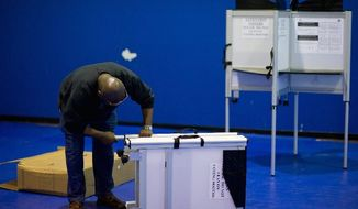 Pollworker Tim Sudbury sets up voting booths Monday in the gymnasium of Lamond Recreation Center in Northwest Washington for Tuesday's D.C. Council primaries. (Andrew Harnik/The Washington Times)