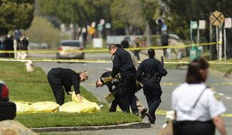 Police cover the bodies of shooting victims at Oikos University in Oakland, Calif., after gunfire erupted at the school Monday morning. The suspect is an Asian male in his 40s who was taken into custody at a shopping center in the neighboring city of Alameda. (Associated Press)