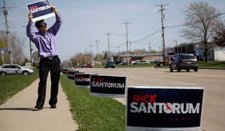 """Corey Essler, a volunteer for former Sen. Rick Santorum of Pennsylvania, a Republican presidential candidate, holds up a sign to woo voters in Menasha, Wis., on Monday. """"You have the opportunity to shock the world,"""" Mr. Santorum said. (Associated Press)"""