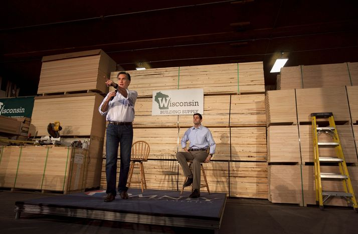 Mitt Romney speaks at a building supply store in Green Bay, Wis., on Monday as Rep. Paul Ryan looks on. (Associated Press)