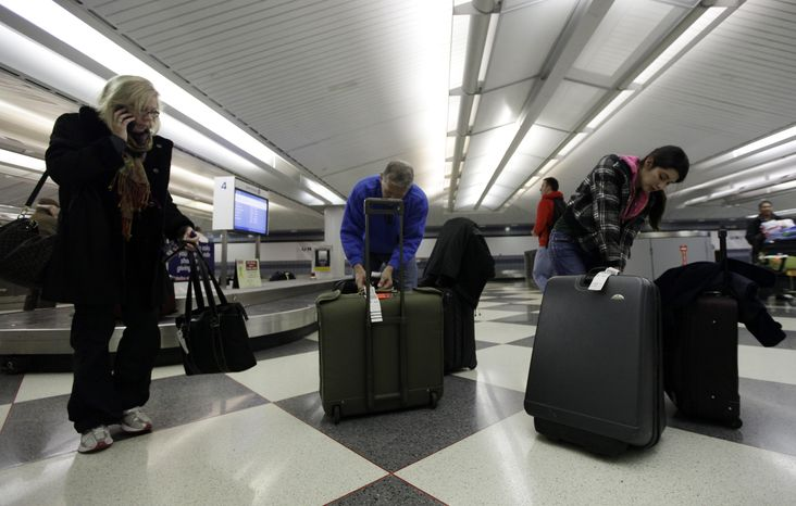 ** FILE ** Air travelers check their luggage at a United Airlines baggage claim area at O'Hare International Airport in Chicago on Thursday, Dec. 22, 2011. (AP Photo/Nam Y. Huh)