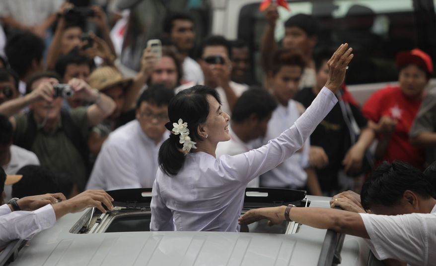 Myanmar pro-democracy leader Aung San Suu Kyi waves to supporters after a brief visit to the headquarters of her National League for Democracy party in Yangon, Myanmar, on Monday, April 2, 2012. (AP Photo/Altaf Qadri)