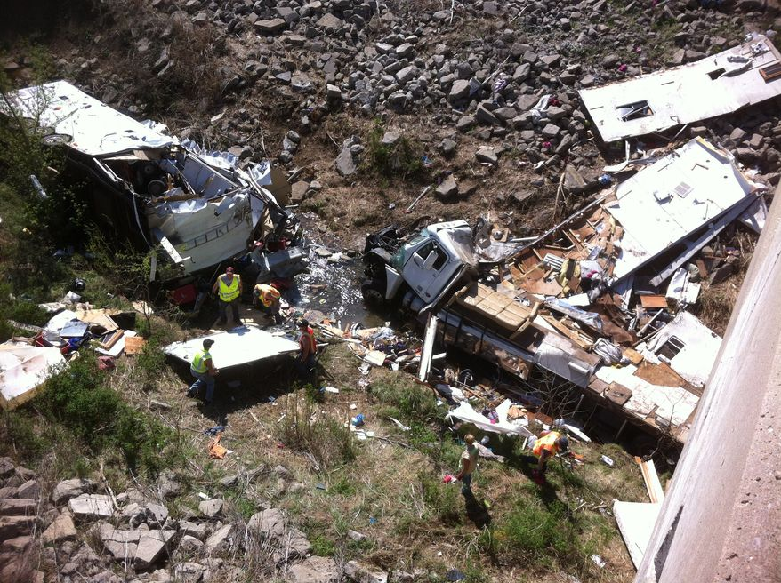 Officials work the scene of a Minnesota-bound motor home on April 1, 2012, in a ravine off Interstate 35 in northeast Kansas. The Kansas Highway Patrol said the northbound Freightliner motor home was carrying 18 people and pulling a trailer when the driver lost control at 9 a.m. that morning and crashed into the ravine. Five were killed. (Associated Press/KMBC-TV)
