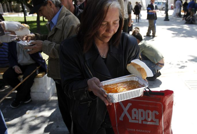 A woman receives a free meal on April 1, 2012, during a soup kitchen organized by a Greek humanitarian group in Athens' main Syntagma square. (Associated Press)